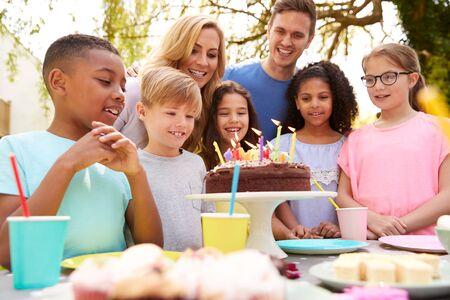 Parents et fils célébrant l'anniversaire avec des amis faisant la fête dans le jardin à la maison