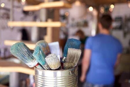 Close Up Of Brushes In Workshop Of Couple Upcycling Furniture