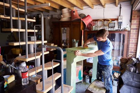 Man In Workshop Upcycling And Working On Fire Surround