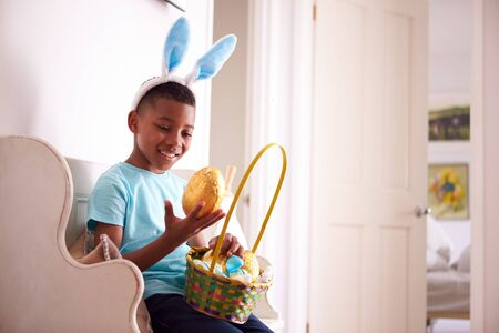 Boy Wearing Bunny Ears Sitting On Seat Holding Chocolate Egg He Has Found On Easter Egg Hunt