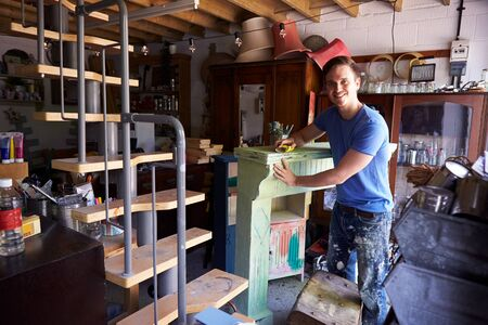 Portrait Of Man In Workshop Upcycling And Working On Fire Surround