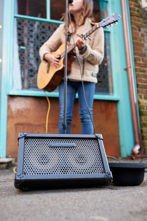 Close Up Of Female Musician Busking Playing Acoustic Guitar Outdoors In Street Stock Photo