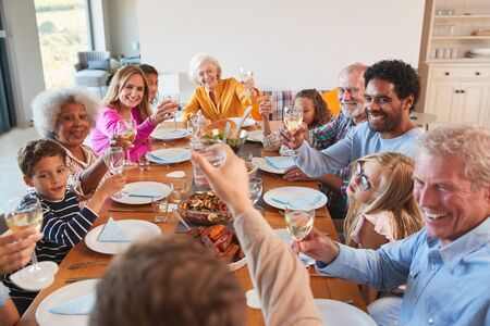 Multi-Generation Family Making A Toast With Wine As They Meet For Meal At Home Фото со стока