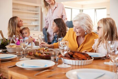 Mother Serving Food As Multi-Generation Family Meet For Meal At Home