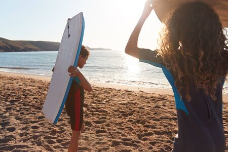 Children Wearing Wetsuits Carrying Bodyboards On Summer Beach Vacation Having Fun By Sea