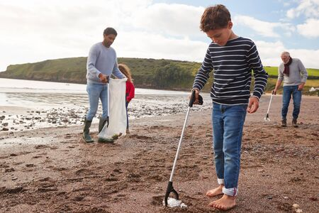 Multi-Generation Family Collecting Litter On Winter Beach Clean Up Zdjęcie Seryjne