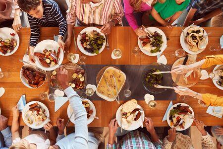 Coup de frais généraux d'une famille multigénérationnelle assise autour d'une table en train de prendre un repas à la maison ensemble Banque d'images