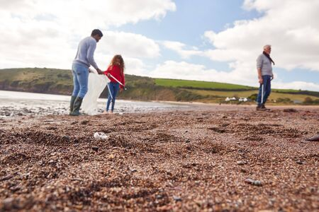 Multi-Generation Family Collecting Litter On Winter Beach Clean Up With Focus On Foreground