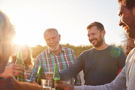 Erwachsene Familie mit mehreren Generationen feiert mit Wein im Winterurlaub am Strand