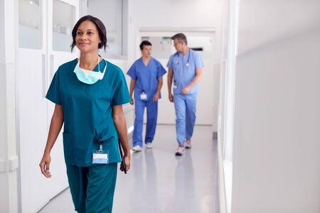 Female Doctor Wearing Scrubs In Hospital Walking Along Corridor Holding Digital Tablet Banque d'images