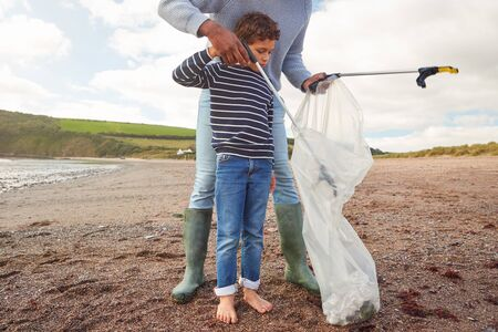 Father And Son Collecting Litter On Winter Beach Clean Up