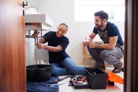 Male Plumber Teaching Female Apprentice To Fix Leaking Sink In Home Bathroom Banco de Imagens