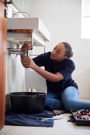 Female Plumber Working To Fix Leaking Sink In Home Bathroom