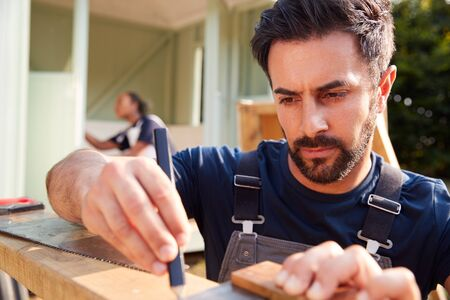 Male Carpenter With Female Apprentice Measuring Wood To Build Outdoor Summerhouse In Garden