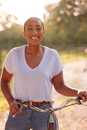 Portrait Of Young Woman Riding Bike Along Country Lane At Sunset
