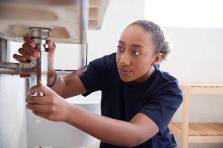 Female Plumber Working To Fix Leaking Sink In Home Bathroom Banco de Imagens