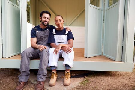 Portrait Of Couple Taking A Break From Building Outdoor Summerhouse In Garden Banco de Imagens
