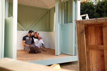 Couple Taking A Break From Building Outdoor Summerhouse In Garden Banco de Imagens