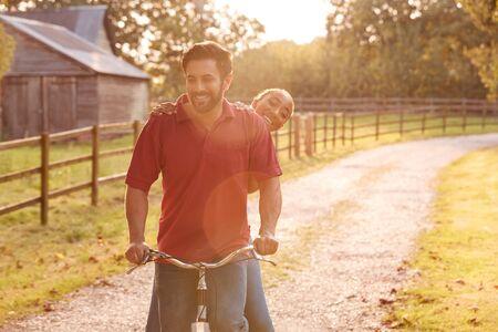 Romantic Couple Riding Bike Along Country Lane At Sunset