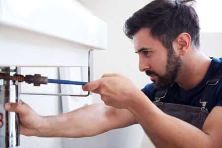 Male Plumber Using Wrench To Fix Leaking Sink In Home Bathroom Reklamní fotografie