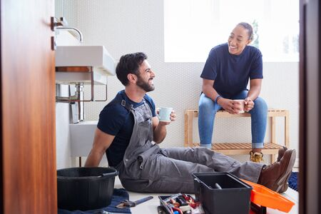 Male Plumber With Female Apprentice Taking A Break From Fixing Leaking Sink In Home Bathroom Stock Photo