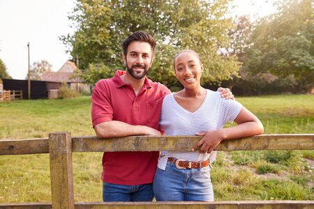 Portrait Of Romantic Couple Taking A Break And Resting On Fence During Walk In Countryside