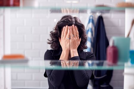 View Through Bathroom Cabinet Of Unhappy Mature Woman Covering Face With Hands