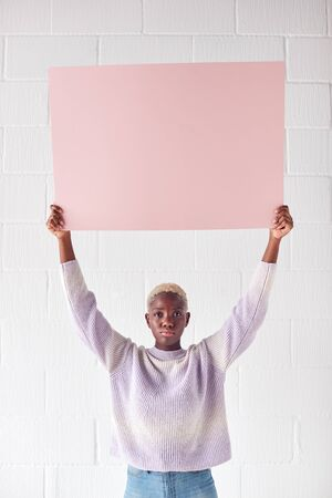 Happy Young Woman Holding Blank Pink Card With Copy Space Above Head White Against White Studio Wall