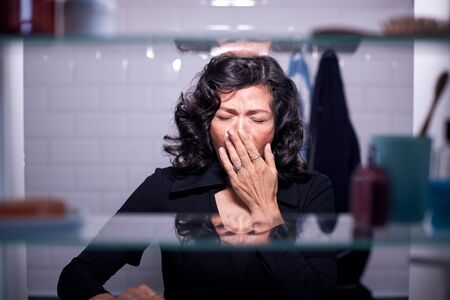 View Through Bathroom Cabinet Of Mature Businesswoman Yawning In Morning Stock fotó