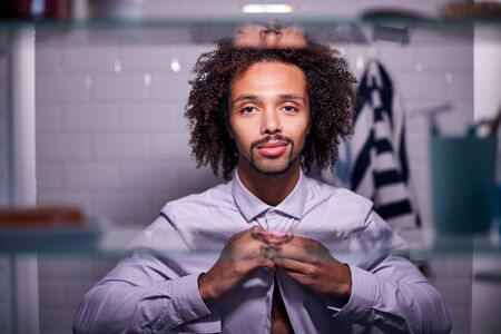 View Through Bathroom Cabinet Of Young Businessman Putting On Shirt Getting Ready For Work