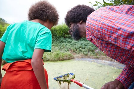 Adult Team Leader Showing Boy On Outdoor Activity Camp How To Catch And Study Pond Life