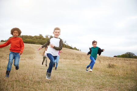 Front View Of Group Of Children On Outdoor Activity Camping Trip Running Down Hill