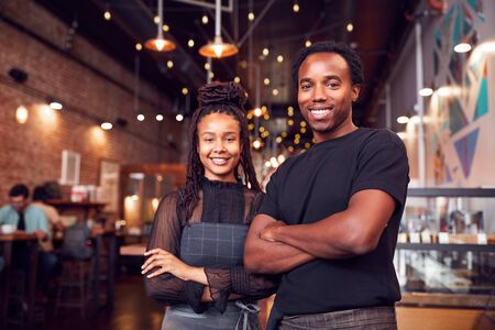 Portrait Of Male And Female Coffee Shop Owners Standing At Sales Desk Stockfoto