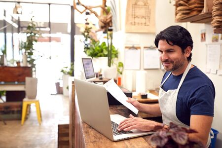Male Sales Assistant Working On Laptop Behind Sales Desk Of Florists Store