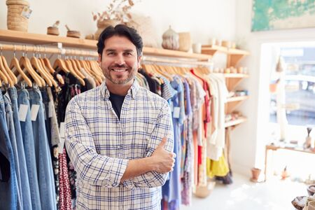 Portrait Of Male Owner Of Fashion Store Standing In Front Of Clothing On Rails