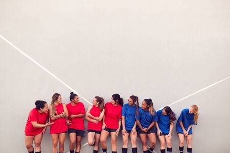 Graphic Shot Of Womens Football Team Leaning Against Wall Whilst Training For Soccer Match Stockfoto