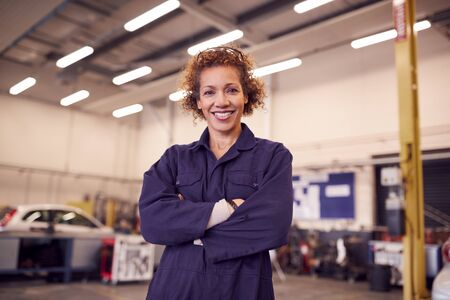 Portrait Of Female Tutor With Safety Glasses Teaching Auto Mechanic Apprenticeship At College