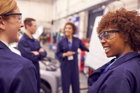 Female Tutor By Whiteboard With Students Teaching Auto Mechanic Apprenticeship At College
