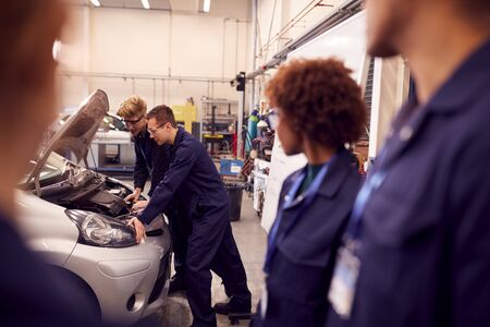 Students Studying For Auto Mechanic Apprenticeship At College Working On Car Engine