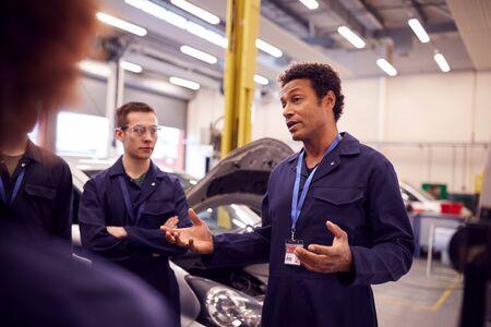 Male Tutor With Students Teaching Auto Mechanic Apprenticeship At College Standard-Bild