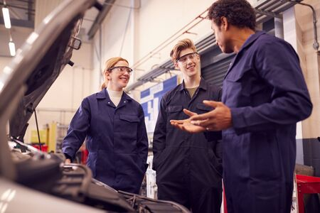 Male Tutor With Students Looking At Car Engine On Auto Mechanic Apprenticeship Course At College Standard-Bild