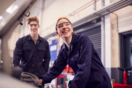 Male And Female Students Looking At Car Engine On Auto Mechanic Apprenticeship Course At College Archivio Fotografico