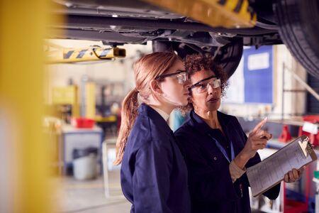Female Tutor With Student Looking Underneath Car On Hydraulic Ramp On Auto Mechanic Course Standard-Bild