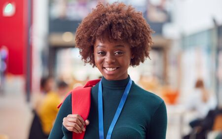 Portrait Of Smiling Female College Student In Busy Communal Campus Building Foto de archivo