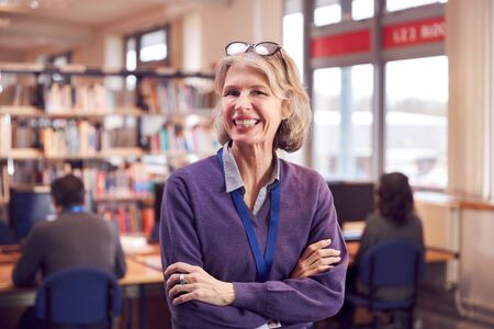 Portrait Of Mature Female Teacher Or Student In Library With Other Students Studying In Background