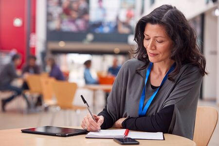 Mature Female Teacher Or Student With Digital Tablet Working At Table In College Hall