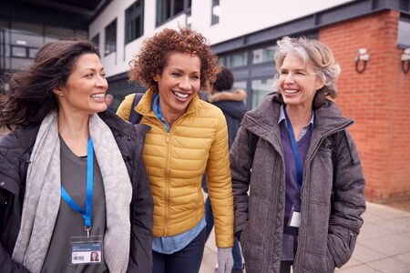 Group Of Smiling Female Mature Students Walking Outside College Building Foto de archivo