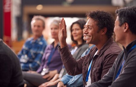 Businessman In Presentation At Conference Raising Hand To Ask Question