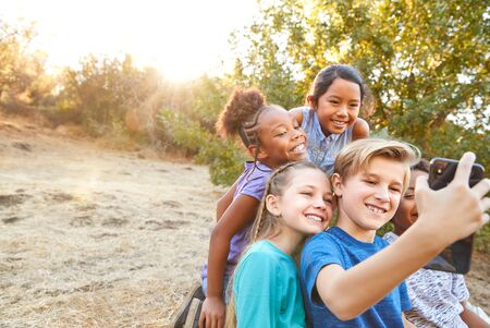 Group Of Multi-Cultural Children Posing For Selfie With Friends In Countryside Together