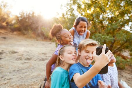 Group Of Multi-Cultural Children Posing For Selfie With Friends In Countryside Together Stockfoto